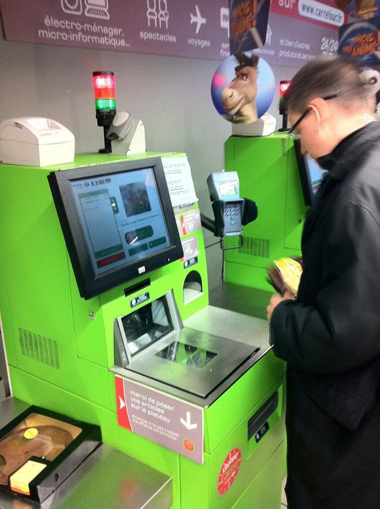 Personne payant à une caisse automatique